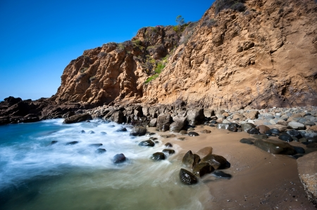 orange county: A secluded cover in Laguna Beavh, California shows the seawater rushing to shore over smooth boulders.