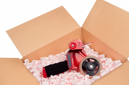 packing supplies: A box full of protective packaging peanuts and a tape dispenser ready to be sealed up for shipping.