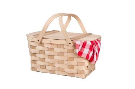 A new wicker and wood picnic basket with a red checkered tablecloth peeking out the side. Isolated on white.