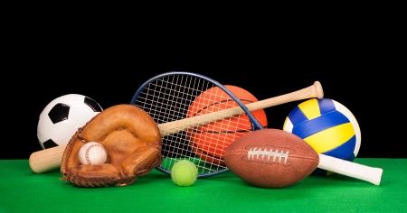 A collection of sports equipment suck as a football, basketball, baseball, tennin racquet, volleyball, soccer ball and catchers glove with a balck background. Stock Photo - 18620348