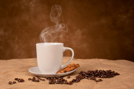 A hot, steaming coffee drink with cinnamon sticks on burlap with room for copy on the backdrop. photo