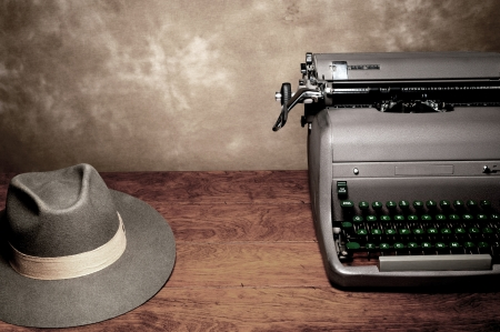An old vintage typewriter with a reporter's fedora hat on a wooden table with room for copy. photo