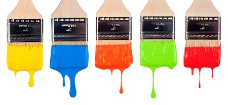 An assortment of paint brushes with dripping, wet paint of varying bright colors. Stockfoto