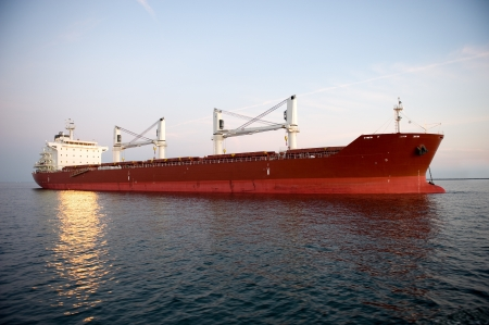 A red shipping transportation freighter anchored just inside a port of call  Stock Photo