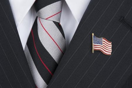 A politician wearing an American flag lapen pin symbolizes patriotism. Foto de archivo