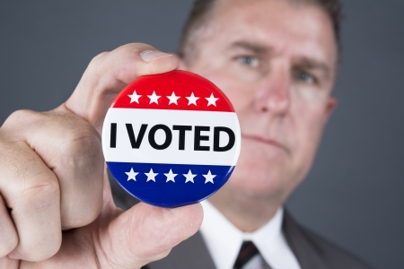 voted: A man who voted holds up his voting badge lapel pin. Stock Photo
