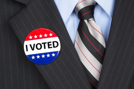 voter: A male voter in his business suit wearing a vote pin on his lapel.