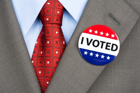A businessman in a tan suit wearing his vote pin on his jacket lapel