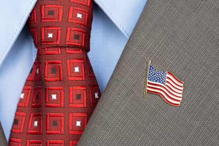 clothes pins: An American flag lapel pin on the collar of a business suit jacket shows patriotism