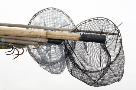 gaff: Two fishing net scoops hanging off of a boat helm  Stock Photo
