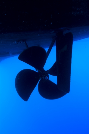 hull: A boat propeller and rudder on a large vessel in blue water  Stock Photo