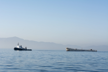 tug boat: A tugboat towing a disabled freighter during an early morning, hazy day