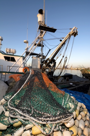 trawler net: A commercial fishing boat with a purse sein net staged for a fishing trip  Stock Photo