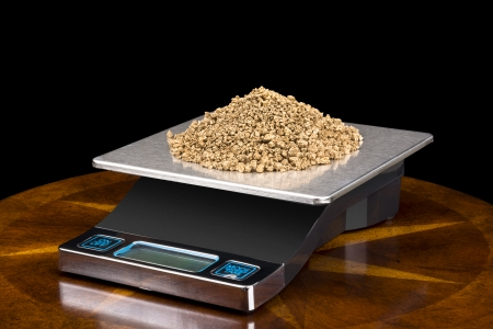 A pile of small gold nuggets on a scale being weighed for their investment value.