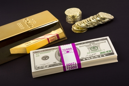 transactional: Gold coins and a gold bar with a pile of American cash for use as any investment or transactional inference.  Cash is motion picture prop money so the serial numbers arent real.