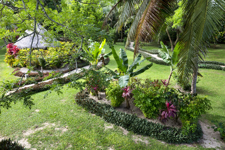 walking path: Lush garden grounds at a tropical resort in Asia shows the relaxing features of a walking path, a cool, shaded cabana and lush growth.