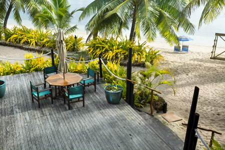 palm lined: A beautiful weathered tropical resort patio sundeck along a beach lined with palm trees and plants. Stock Photo