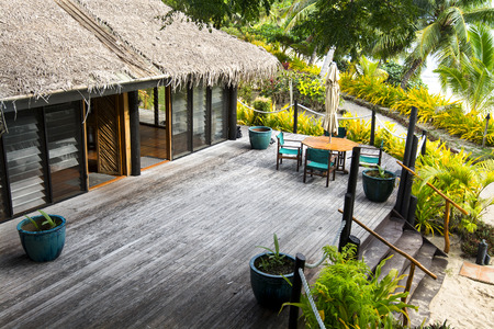palm lined: A tropical resort lodge with wooden patio sundeck along a beach lined with palm trees