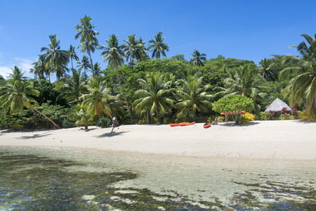 fijian: A look at a Fijian tropical resort from the water showng its lush surroundings and recreational kayaks on the beach along with a small, thatched cabana for changing and getting out of the sun. Stock Photo