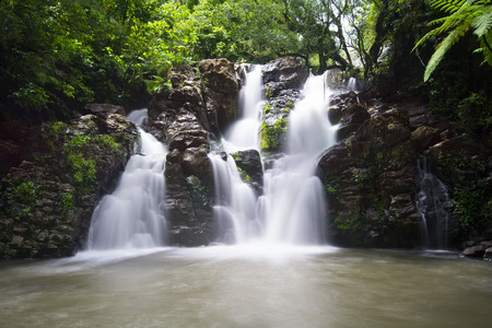 fiji: Image using slow shutter speed to capture the motion of Bouma Falls in Fiji and its beautiful surrounding pool of fresh water.