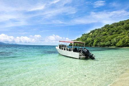 green boat: A scuba diving boat is anchored in a beautiful tropical bay of turquoise water and a bright, blue vibrant sky with patchy clouds. Stock Photo