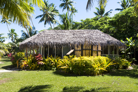 south pacific: A traditional bure, or lodge, at a south pacific island resort surrounded by lush, green gardens.