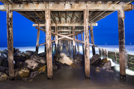 underneath: An image of the Balboa Pier in Orange County California early in the morning shows the structural detail and surrounding beauty of the ocean   Shot using a technique called light painting