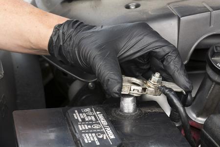Ein Mechaniker installiert ein sauberes Batterieklemme mit einem Schraubenschlüssel, um das Kabel auf die Post während der routinemäßigen Wartung Automobil sichern