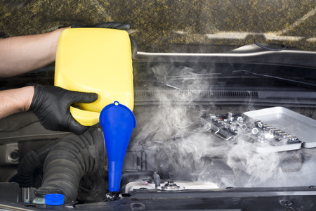 A mechanic pours engine coolant into an overheated automobile radiator in an attempt to cool it down and stop the steam   Stockfoto