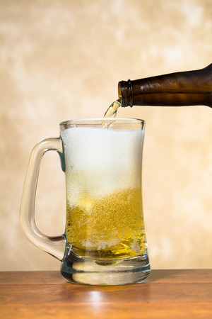Ice cold, refreshing beer being poured into a classic pint beer mug shows the tasty white froth and golden brew. Stock Photo