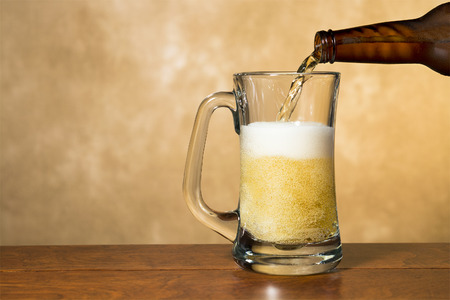 Fresh, cold, crisp beer being poured into a classic pint mug against a mottled golden background. Stock Photo