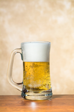 A beer mug freshly filled with cold, crisp beer with a nice foam head. Stock Photo