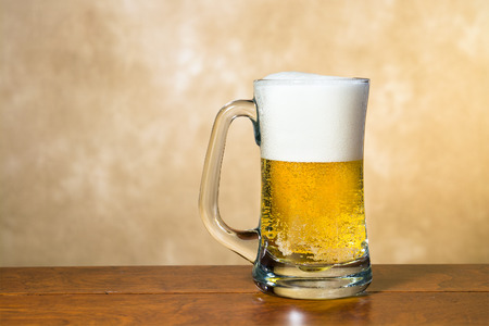A cold, crisp mug of beer in a traditional pint glass with a foamy head