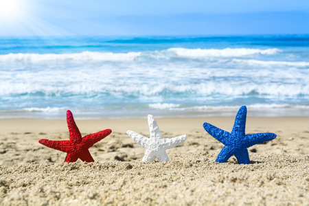 red white blue: Conceptual summer holiday image of three red, white and blue starfish on the beach overlooking a turquoise ocean while celebrating the July fourth holiday. Stock Photo