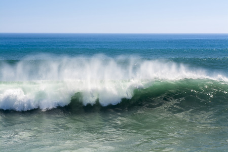 wave crest: A beautiful and powerful turquoise wave in high winds curls while white spray mist forms and at its crest in Huntington Beach.