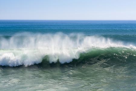granola: Una onda hermosa y poderosa turquesa con vientos fuertes se queja mientras blancas formas niebla del aerosol y en su cresta en Huntington Beach.