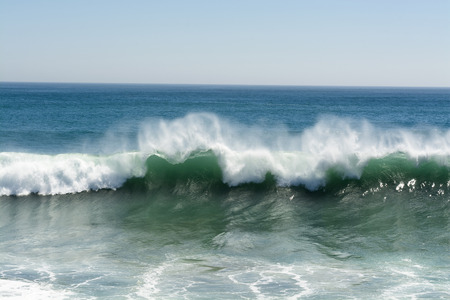 orange county: A beautiful and powerful turquoise wave in high winds curls while white spray mist forms and at its crest in Huntington Beach.