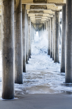 pilings: Waves generated by a storm rush through the underside of a pier, creating rough, turbulent water as it moves through the pillars to the beach. Stock Photo