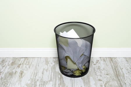 wads: An office trashcan filled with wads of crumpled paper, sticky notes and folded paper.