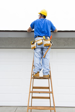 A contractor walks up a ladder to inspect the rook of a residential home during an overcast day Stockfoto
