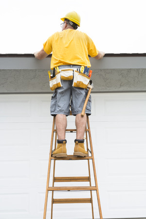 A contractor with a belt full of tools walks up a ladder to inspect the roof of a residential home. photo