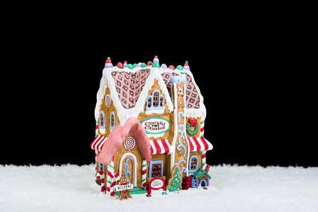 casita de dulces: Una casa de pan de jengibre en la nieve aislada en un fondo negro se puede utilizar como un elemento de diseño o, simplemente, para la colocación de la copia.