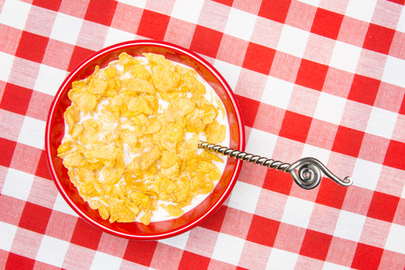 A red bowl of cornflakes and milk on a classic, red, checkered tablecloth ready as a breakfast meal.