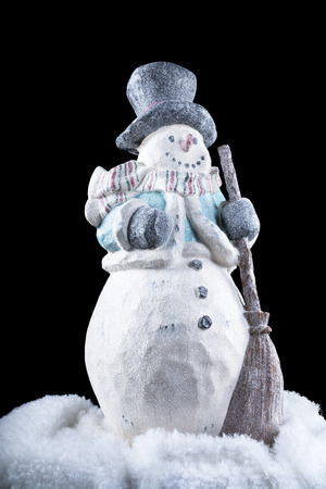 cold season: A decorative snowman in the dark, cold outdoors during the holiday season.