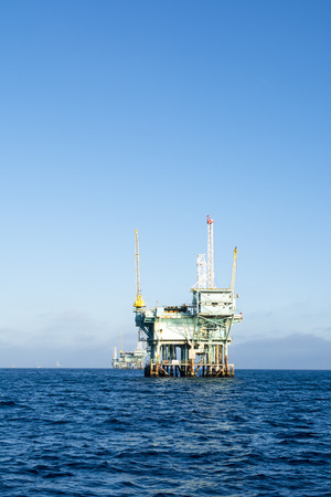 il: An offshore oil platform rests in deep ocean water on a clear, bright, sunny day.