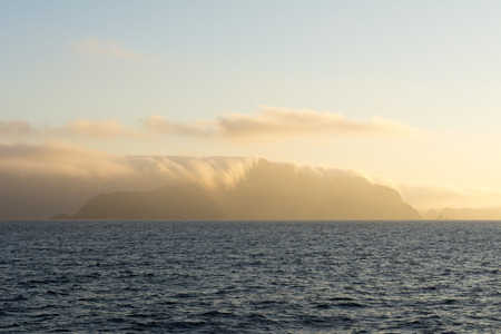 engulfed: Santa Cruz Island in California's Channel Islands is engulfed with early morning cloud cover as it is lit by orange sunlight.