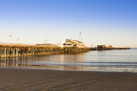 santa barbara: A low, setting sun casts a deep orange light on the pilings of the Santa Barbara pier, also know as Stearns Wharf. Stock Photo