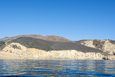 A remote island in the Channel Islands of California shows the geology of rugged, diverse terrain framed against deep turquoise water and a vibrant blue sky.