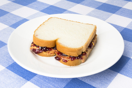 peanut butter and jelly sandwich: A delicious peanut butter and jelly sandwich with grape jam ready to be eaten during lunchtime. Stock Photo