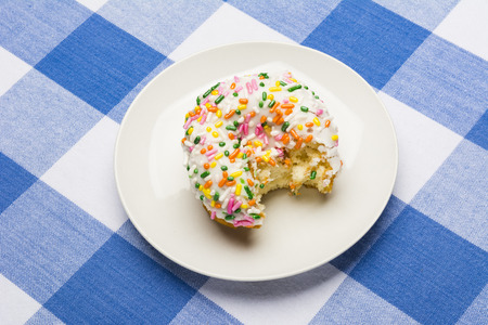checker plate: A freshly bitten, delicious icing coated cake donut with sweet sprinkles on a classic, checkered diner tablecloth Stock Photo